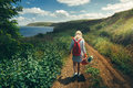 Young Girl Tourist, View From Behind, Walking Along The Road Towards The Sea Concept Of Hiking And Adventure Stock Images - 94375424