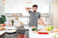 Confused Handsome Man Cooking Vegetable Salad In Kitchen Royalty Free Stock Photography - 94399387