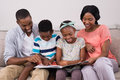 Family Reading Magazine While Sitting On Sofa At Home Royalty Free Stock Image - 94439636