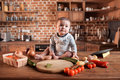 Boy Sitting On Kitchen Table Around Of Raw Vegetables Before Cooking A Dinner Stock Images - 94444514