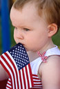 Young Girl Holding An American Flag And Riding In Red Wagon Having Fun In The Park For July Fourth Royalty Free Stock Photography - 94479267