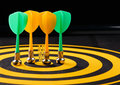 Magnetic Dart Arrows On Yellow Dart Board. Black Background Stock Images - 94922434