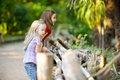 Two Cute Little Sisters Watching Animals In The Zoo On Warm And Sunny Summer Day. Children Watching Zoo Animals Standing By The Fe Stock Photos - 95157283
