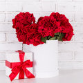 Beautiful Red Flowers And Gift Box Over Brick Wall Stock Photo - 95217680