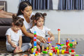 Young Mother And Two Little Girl Play Wooden Toys Blocks On The Stock Photo - 95247150
