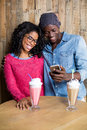 Smiling Couple Using Mobile Phone Against Wooden Background Stock Photography - 95481042