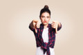 Dislike. Young Unhappy Upset Girl With Casual Style And Bun Hair Thumbs Down Her Finger, On Beige Blank Wall With Copy Space Stock Image - 95512231