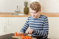 Boy Chopping Carrots On Cutting Board In Kitchen Royalty Free Stock Photography - 95534917