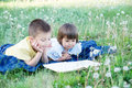 Children Reading Book In Park Lying On Stomach Outdoor Among Dandelion In Park, Cute Children Education And Development Stock Images - 95562734