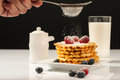 Belgian Waffles With Raspberries And Sieving Sugar Powder And Honey Served With Jug Of Milk On A White Table Royalty Free Stock Photo - 95883645