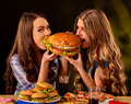 Women Eating Fast Food. Gils Eat Hamburger With Ham . Stock Images - 95890964
