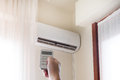 Air Conditioner And Hand With Temperature Remote Control Stock Photo - 95917300