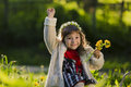 Cute Young Girl Wearing Wreath Of Dandelions And Smiling While Sitting On Grass In Park Royalty Free Stock Images - 95920669