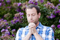 Close Up Of Man Praying Alone In Front Of Purple Flowers. Stock Photo - 96065210