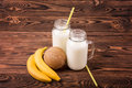 Milk And Fruits On A Brown Background. Delicious Bananas And A Nutritious Coconut. Two Mason Jars With Tasty Milk. Stock Images - 96073254
