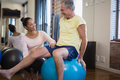 Smiling Female Therapist Crouching By Senior Male Patient Sitting On Exercise Ball Stock Photography - 96122252