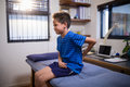 Boy Frowning With Backache While Sitting On Bed Stock Photos - 96124253