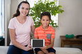 Portrait Of Smiling Female Therapist Showing Digital While Sitting With Arm Around Boy On Bed Stock Photo - 96124710