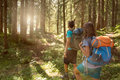 Man And Woman With Backpack Walking On Hiking Trail Path In Forest Woods During Sunny Day.Group Of Friends People Summer Stock Photos - 96132753