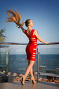 A Hot Girl On A Natural Background. An Elegant Lady On A Hotel Terrace In Summer. A Girl In A Red Dress Is Looking At The Sea. Royalty Free Stock Image - 96232926