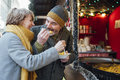 Elderly Couple Eating At Christmas Market Stock Photo - 96260770