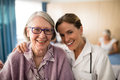 Portrait Of Smiling Female Doctor Standing Arm Around Senior Woman Stock Photography - 96361032