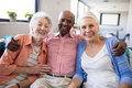 Portrait Of Senior Man Sitting With Arm Around Over Females Stock Photography - 96362162