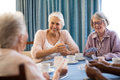 Smiling Senior Female Friends Playing Cards Royalty Free Stock Photography - 96364147