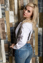 Beautiful Sexy Girl With Big Boobs In A Vintage Blue Jeans And White Shirt Poses Near A Wooden Wall. Royalty Free Stock Photography - 96402117