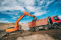 Heavy Machinery Working On Construction Site - Excavator Loading Dumper Trucks During Roadworks At Highway Stock Image - 96447611