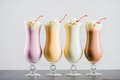 Row Of Various Sweet Milkshakes With Cherries In Glasses Stock Photo - 96456510