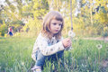 Funny Little Girl, With Serious Face, Is Looking At A Dandelion Royalty Free Stock Photo - 96462945