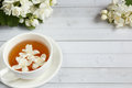 Cup Of Tea, Pouring Honey From A Spoon In A Jar, Jasmine Flowers On A Light Wooden Background. Copy Space Royalty Free Stock Photography - 96482897