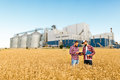 Two Farmers Stand In A Wheat Field With Tablet. Agronomists Discuss Harvest And Crops Among Ears Of Wheat With Grain Stock Photo - 96635770