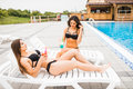 Two Beautiful Women Are Lying On Chaise-longue Poolside Outdoors And Talking. Summer Time Stock Photos - 96713683