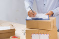 Courier Making Notes In Delivery Receipt Among Parcels At Table Stock Images - 96736044