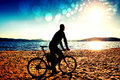 Film Grain. Young Man Cyclist Sit On Bike,  Blue Sky And Sunset Background On Beach. End Of Season At Lake And Popular Tourist Res Royalty Free Stock Images - 96763839
