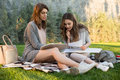 Smiling Young Two Women Sitting Outdoors In Park Writing Notes. Stock Photo - 96800930