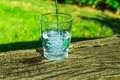 Process Of Pouring Pure Clear Water Into A Glass From Top, Wooden Log, Green Grass In The Background, Outdoors, Health, Hydration Stock Images - 96917274
