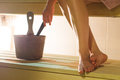 Woman In Sauna Holding Ladle About To Throw Water From The Bucket To The Stove. Royalty Free Stock Photo - 96917765