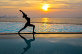 Silhouette Young Woman Practicing Yoga On Swimming Pool And The Beach At Sunset Stock Photos - 96959623