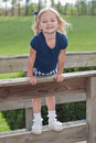 Smiling Girl Standing On The Fence Royalty Free Stock Photos - 9700478