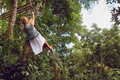 Woman Flying High On Rope Swing On Wild Jungle Background Stock Images - 97039804