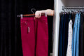 Woman Trying On Pants In A Clothing Store Reaching Out Hand From A Fitting Room Holding Trousers Royalty Free Stock Photo - 97068945