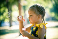 Little Girl Play In Park Blow Soap Bubbles Profile Close Up Stock Photo - 97144260