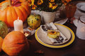 Autumn Traditional Seasonal Table Setting At Home With Pumpkins, Candles And Flowers Stock Image - 97155971