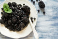 Plate With Blackberries And Blueberries On Blue Wooden Background Stock Photo - 97229650