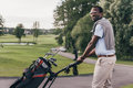 African American Man In Sunglasses Walking With Bag Full Of Golf Clubs Royalty Free Stock Photography - 97288047