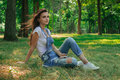 Lovely Girl Sits On Green Grass And Her Hair Fly Away In The Wind Stock Image - 97307331