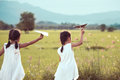 Back View Of Two Asian Child Girls Playing Toy Paper Airplane Stock Photography - 97328962